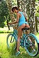 A girl Susi with short hair in a blue dress and no panties on a blue bicycle in the park.